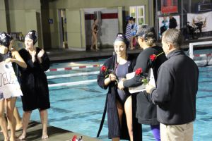 Coach Kirsten Frazer hands out roses and posters to senior players on Senior Night