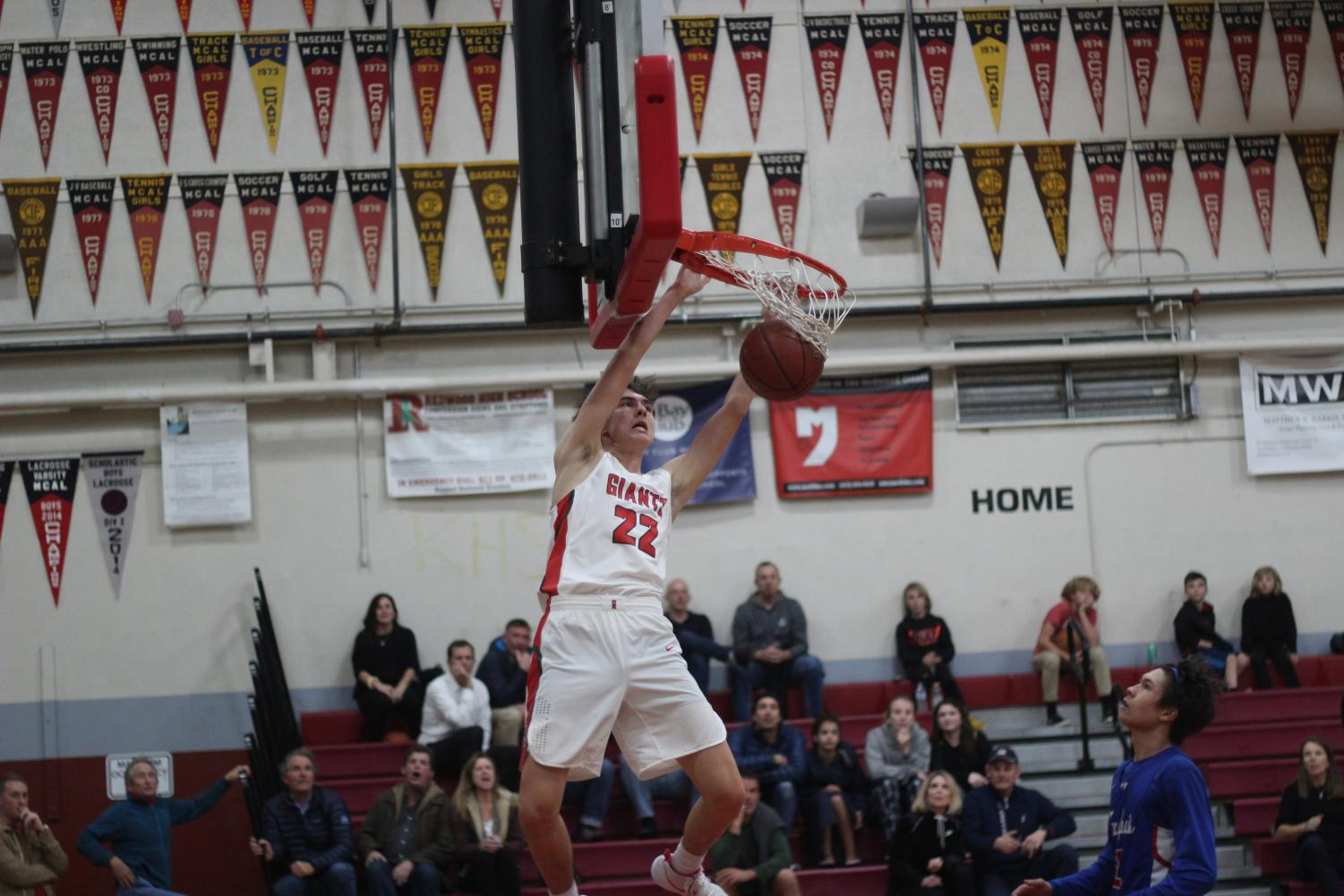 Brandon Radu throws a dunk against Tam High School.