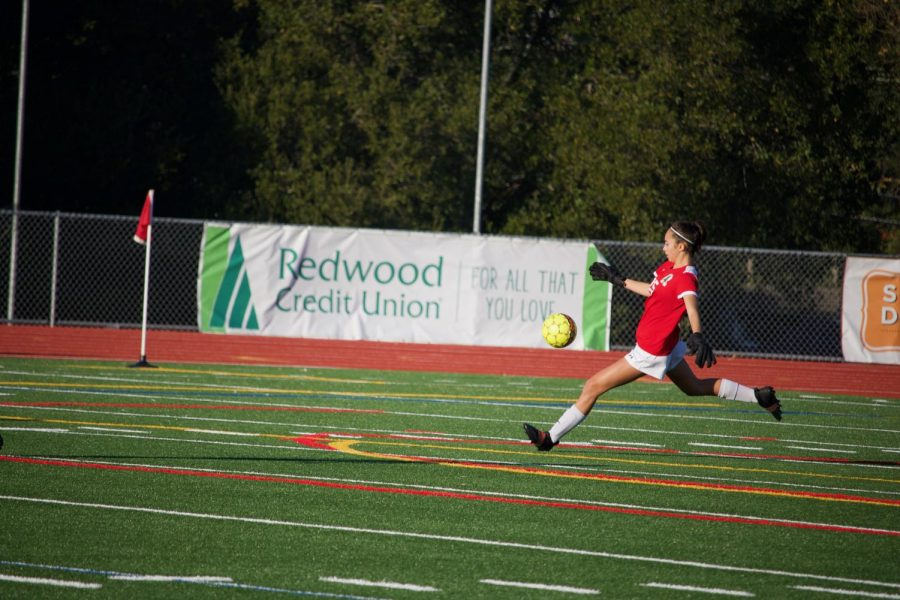 Mia Harmant kicks the ball back into the game after defending the goal.