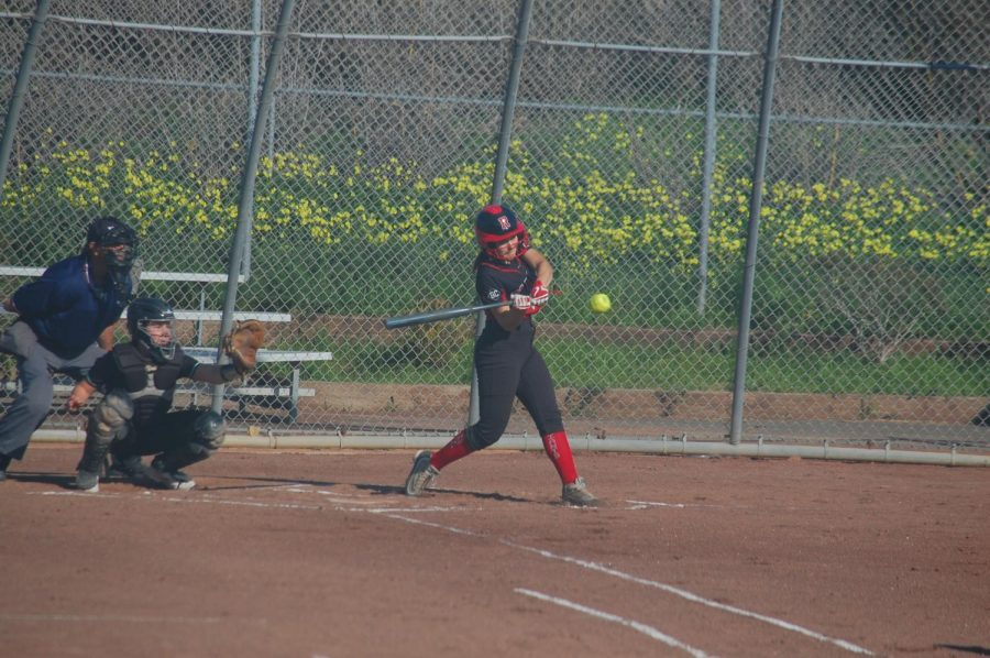 Sophomore Morgan Bello hits the ball, bringing her teammate home.