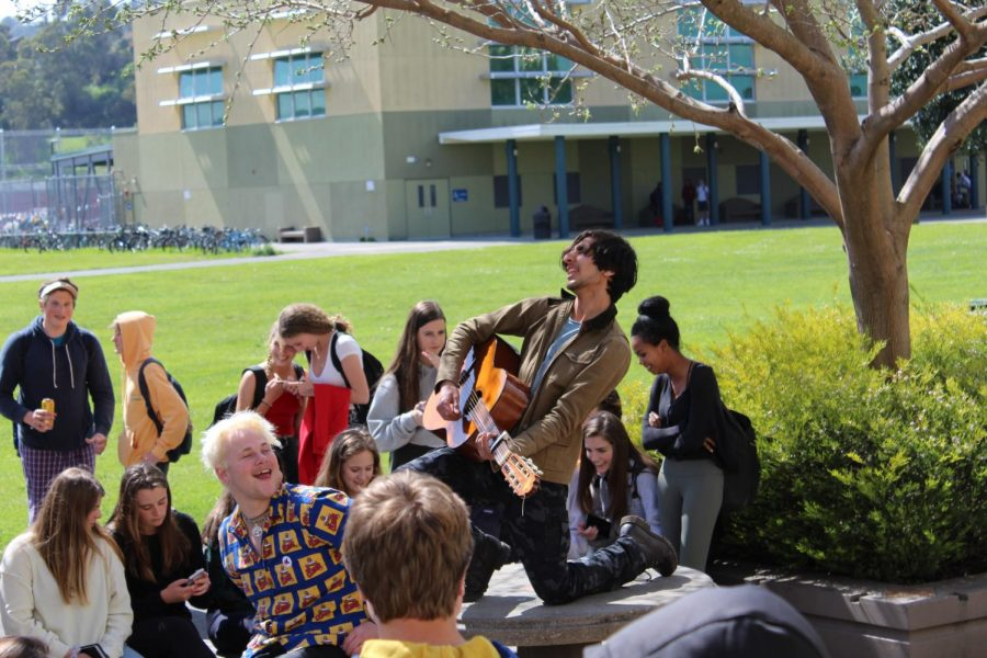 Freshman plays guitar in front of peers outside CEA.