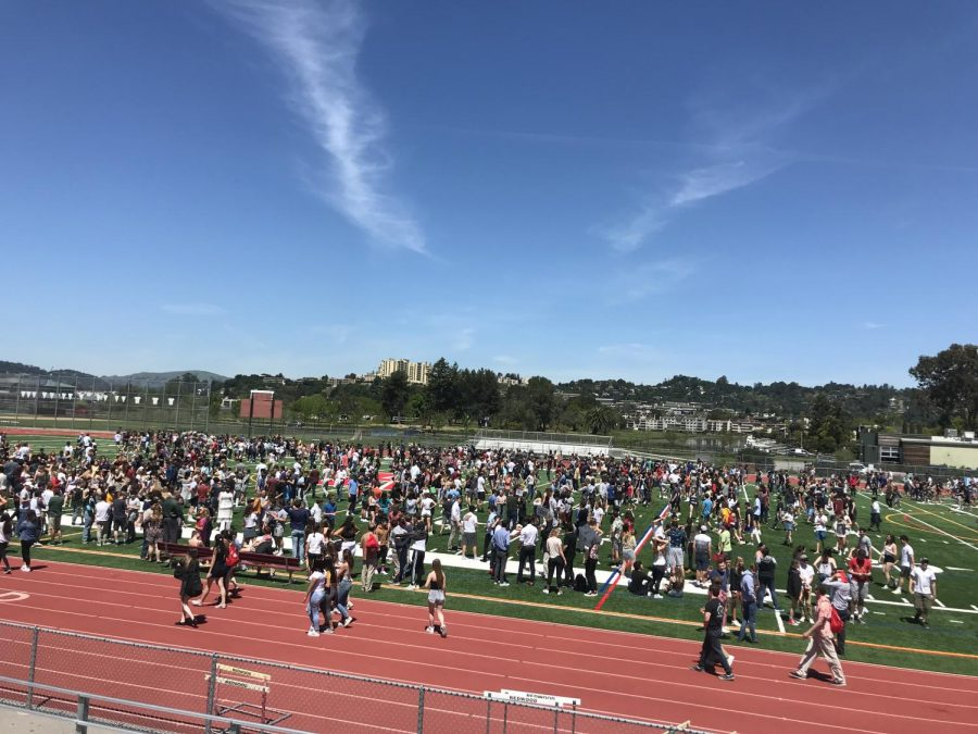 Students congregate on the field for a schoolwide evacuation drill as temperatures reach 85 degrees.