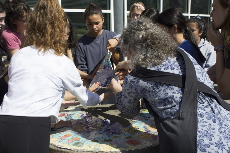 Carefully laying down tiles on the cement-covered table, the Art Honors Society takes advantage of the sunny day.