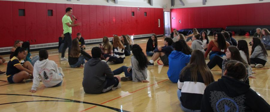 Sitting on the ground, students participate in the Breaking Down the Walls workshop in the small gym.