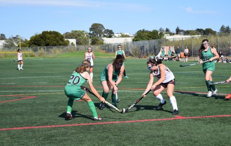 Redwood fights for possession of the ball, clashing with the two opposing Pirates.