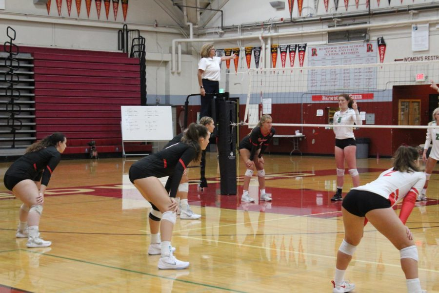 In ready positions, the team sets up to receive a serve from Drake High School.
