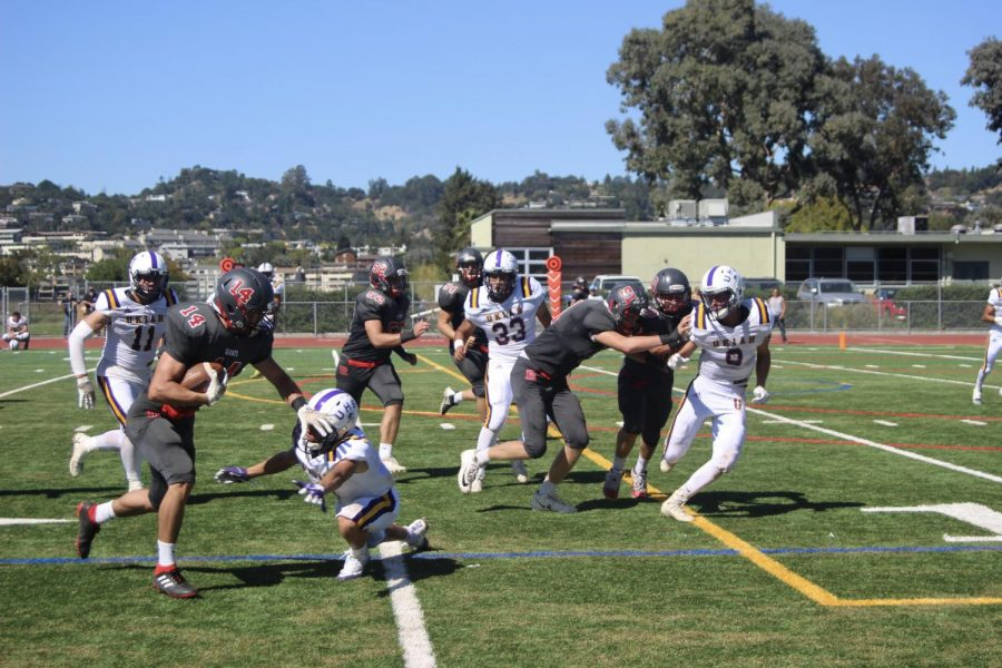 Wide receiver Maximo Tribuzio (14) avoids a Wildcat defender as he barrels down the field