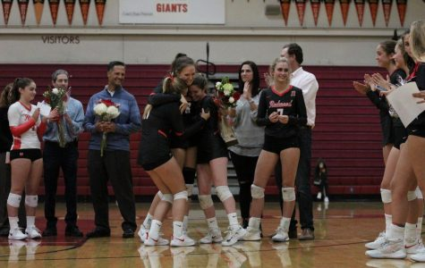 Juniors Grace Mathews and Ryan Bludau embrace senior Jordan Perry in a hug