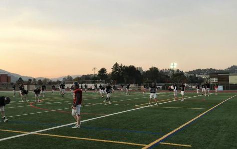 Beginning their warmup, the varsity football team practices under the lights due to soccer tryouts and daylight savings.