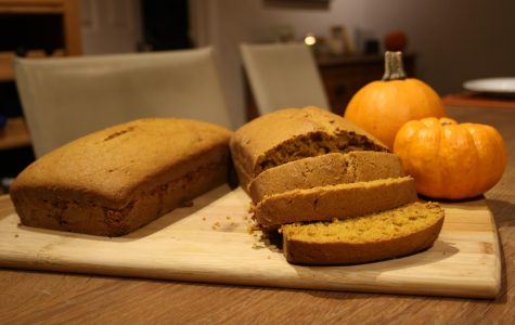 A sliced loaf of pumpkin bread perches atop a table, waiting to be eaten.