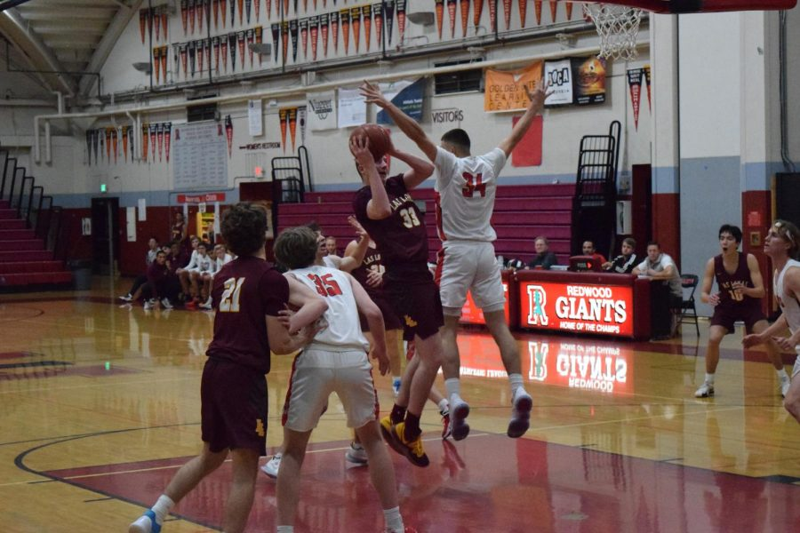 The Redwood boys' varsity basketball team leaps to block a shot from the opposing team of Las Lomas.