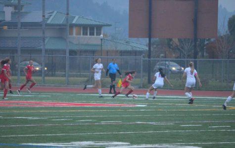 The girls' varsity soccer team battles Tamalpais High School through the rain.