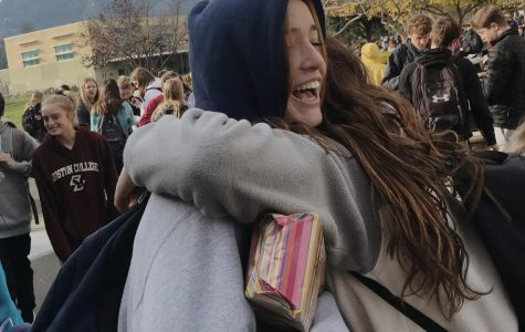Students embrace and smile after completing their first final of the fall semester