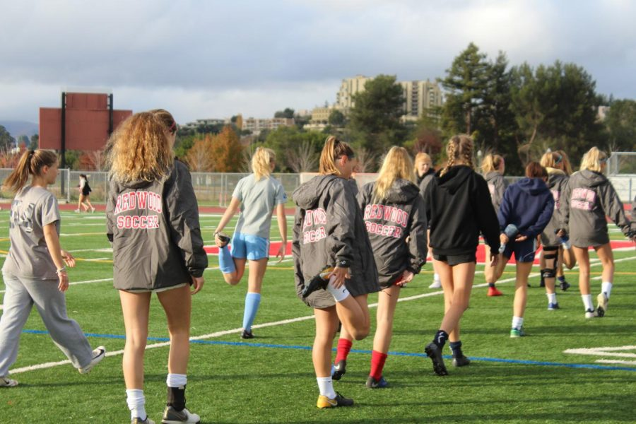 In order to prevent injury, the girls' varsity soccer team stretches their quads during a dynamic warm up.