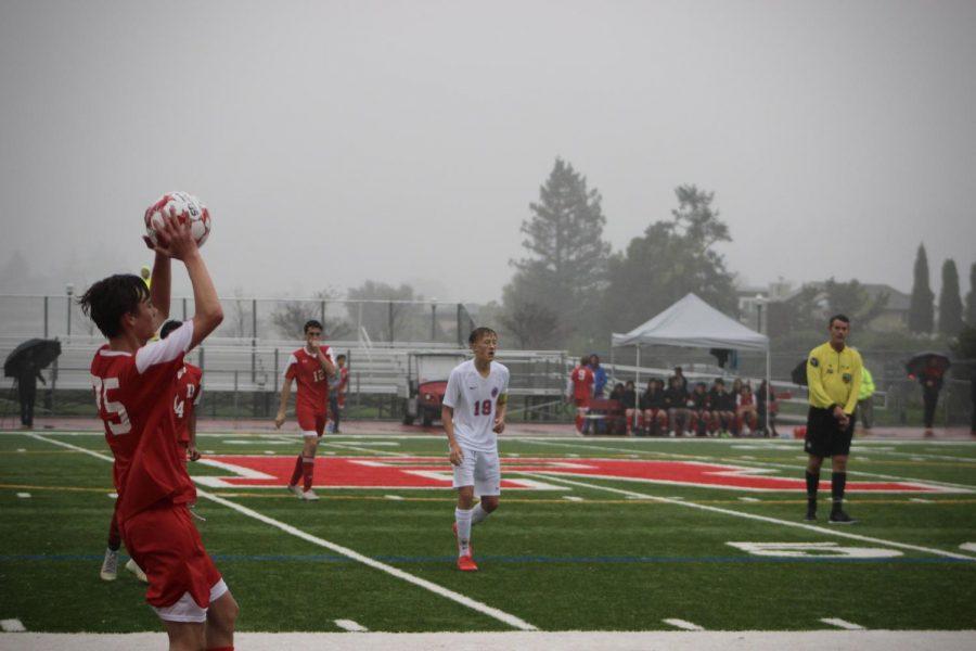 Varsity player Miles McGrath preparing his throw-in during a rainy game against Tam.