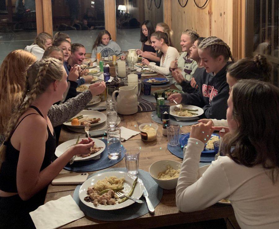 The girls' varsity soccer team eats dinner in Lake Tahoe, spending time together for team bonding.