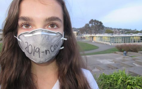 A student stands in front of Redwood's amphitheater wearing a mask in solidarity with people infected with the novel coronavirus