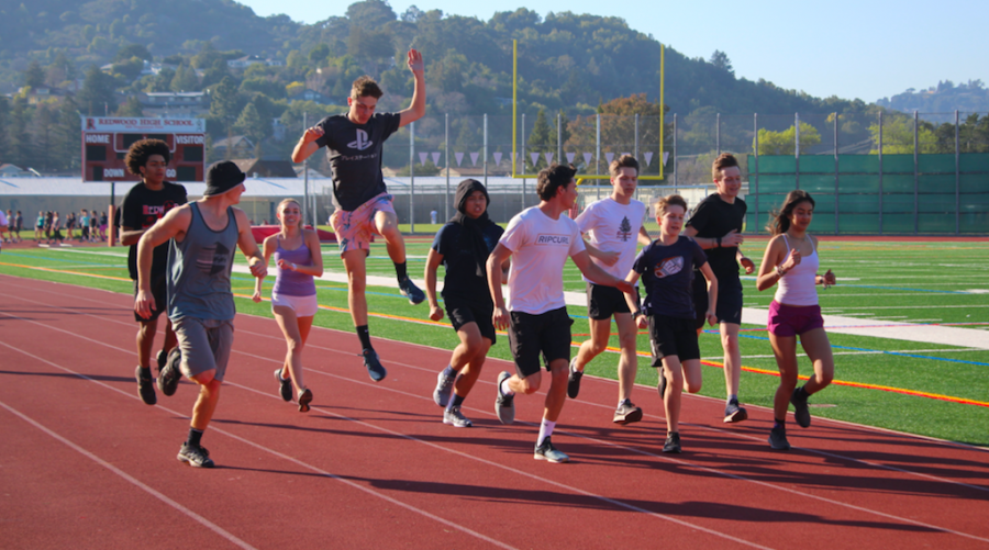 Warming up for practice, members of the track and field team run together.