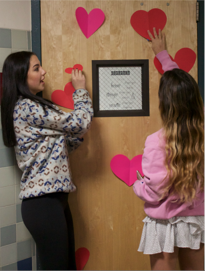 Adorning classroom doors with paper hearts, Link Crew and Leadership collaborate to decorate the hallways for Valentines Day.