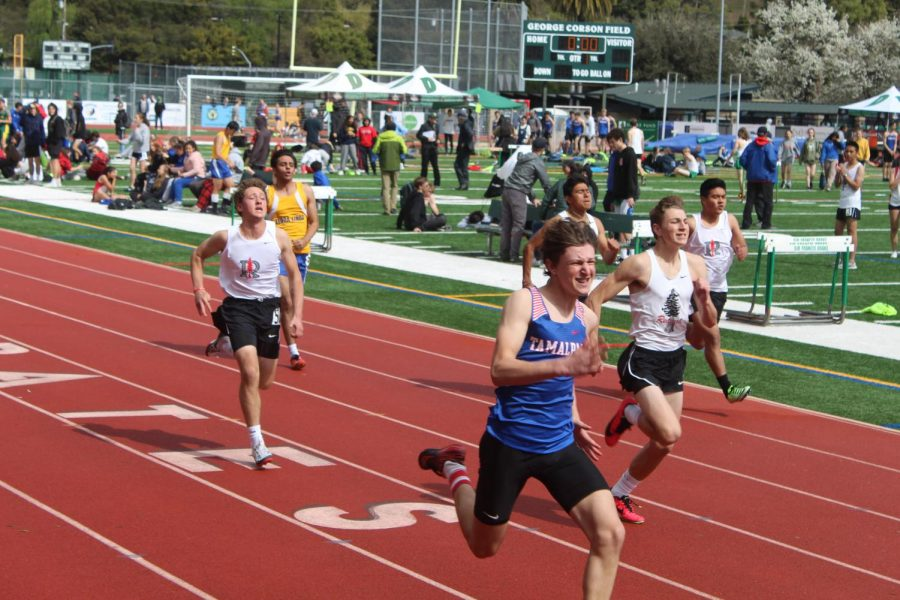 Redwood boys sprint towards the finish line of the 100 meter dash at the first track meet of the season.