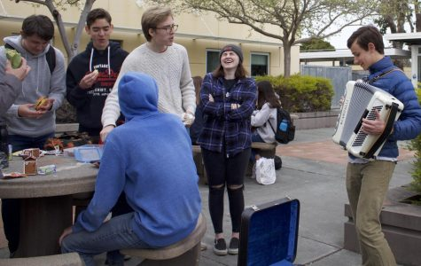 Playing the accordion at lunch, students gather around junior Bennett Somerville to listen to his music.