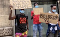 Los Manifestantes usan máscaras y sostienen carteles coloridos en diferentes idiomas.