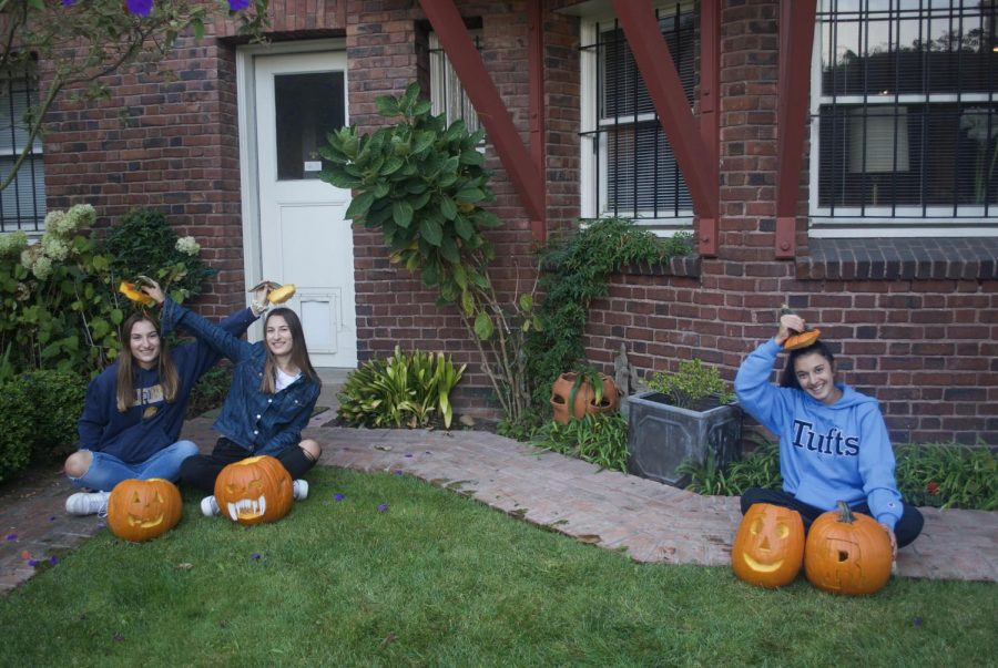 Juniors Lauren, Claire Mckechnie and Sophia Pero sit six feet apart outdoors while carving pumpkins.