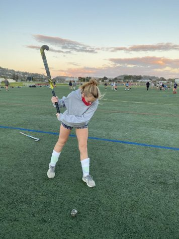 Winding up for a pass, junior Liv Holscher practices alongside her teammates for what should have been the field hockey team