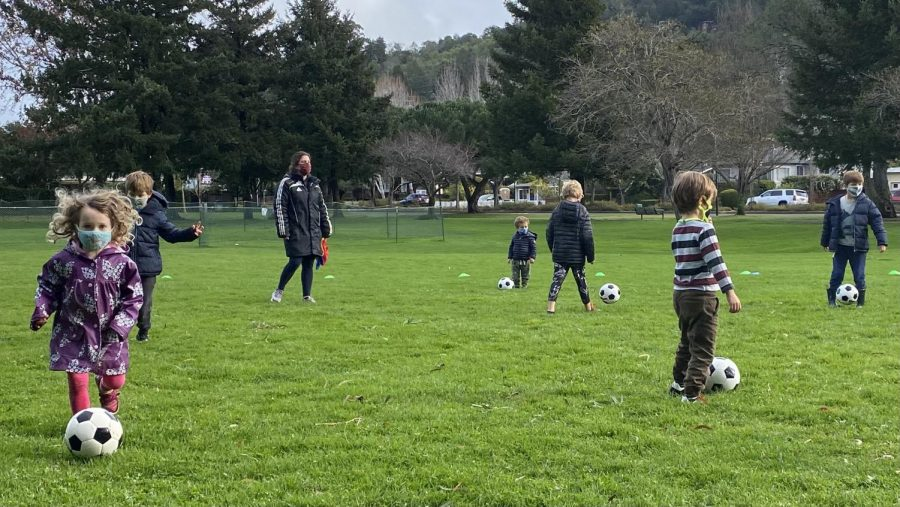 Taking the opportunity of a break from the rain, Marin kids gather in small cohorts to safely play soccer.