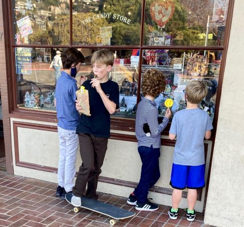 On a sunny day, a group of young boys gather outside of a candy store on Main Street in Tiburon to enjoy their sweets and their friends.