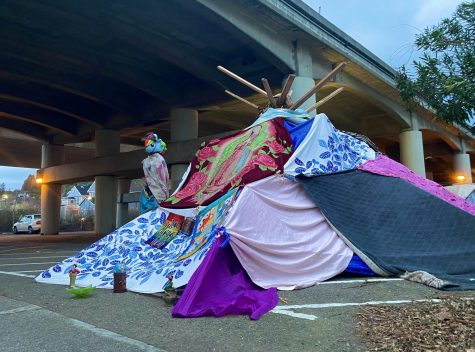Sheltering from the rain, a homeless man sets up camp beneath Highway 101 in downtown San Rafael.