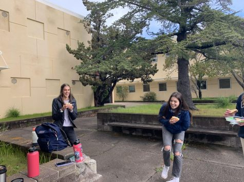 Redwood Juniors Ava Converse and Emily Fieber have a socially distant lunch in the rain.