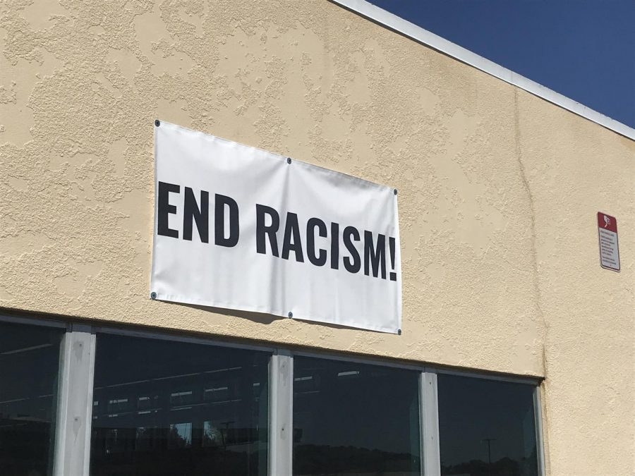 A poster condemning racism stands outside Redwood campus.