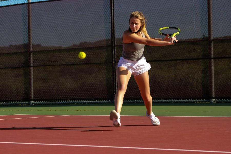 Returning a shot to her opponent, Erin Roddy winds up for her backhand.