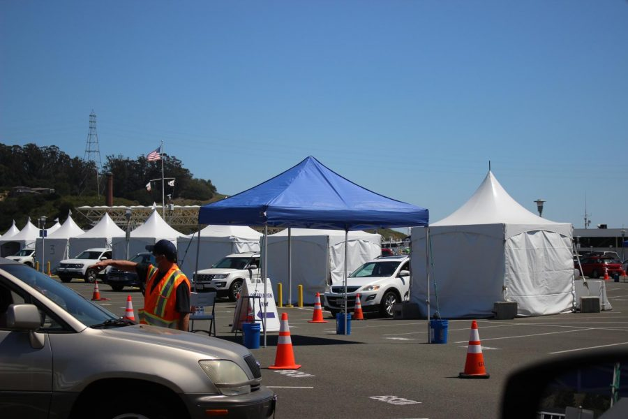 A long line of cars follow the traffic cones as they are directed through the Larkspur Ferry landing's COVID-19 vaccination site, newly open to those 16 years old and up in Marin County.