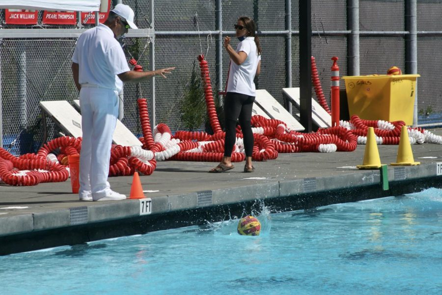 The ball is dropped in the middle of the pool by a referee at the girls JV water polo game, signaling the start of the game.