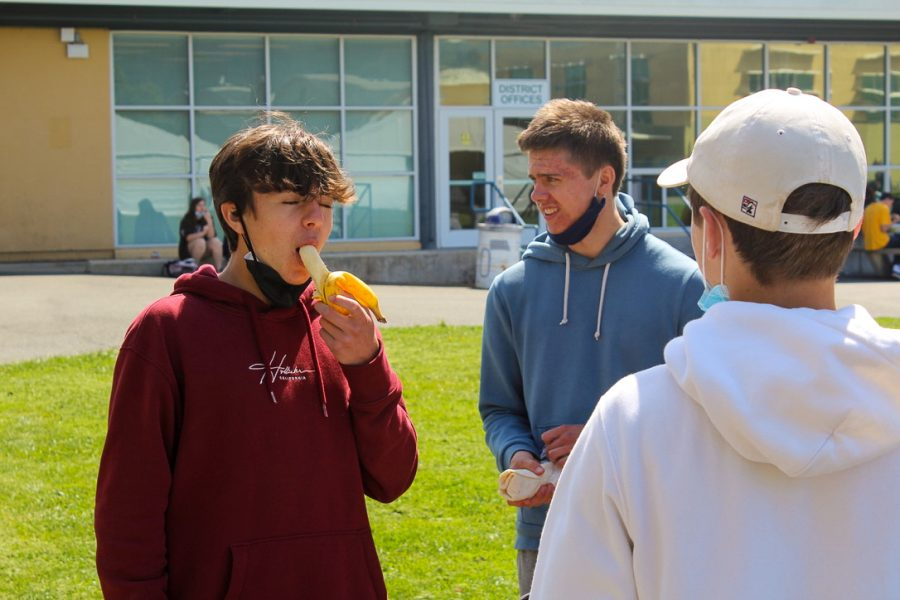Sophomore Nick Pes dives into his banana while enjoying a meal with friends.