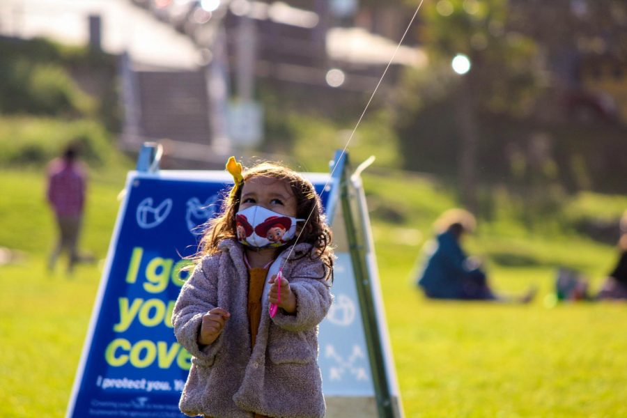 Face covered by a Toy Story-themed mask, this young girl highlights innocence as she playfully smiles up at her kite.