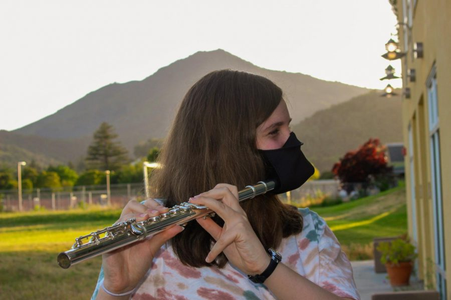 Warming up, senior Emily Rusting wears a special mask made for flute players.