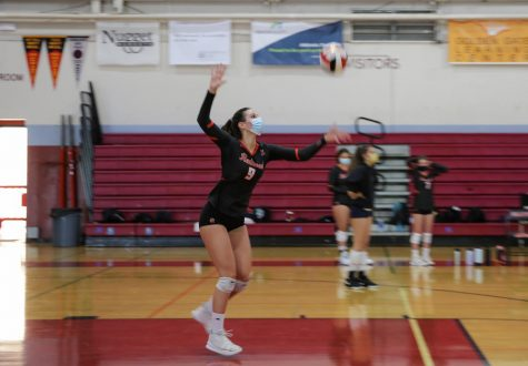 Launching the ball into the air, Green serves across the court at a home game against San Rafael High School.