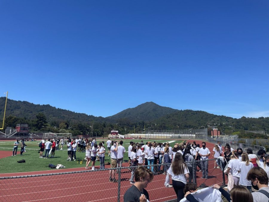 Gathering on the football field, seniors sign each others shirts before graduating in a week.