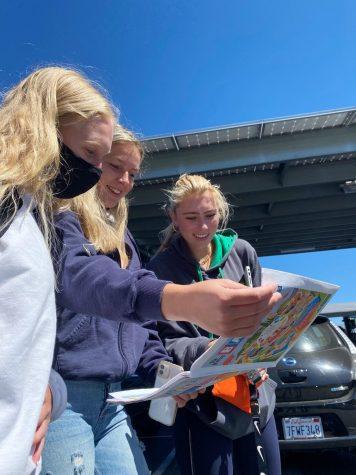 Seniors Rachel mueller, Lindsay Felder and Fiona Peterson enjoy reading the senior edition of the Bark in the senior lot.