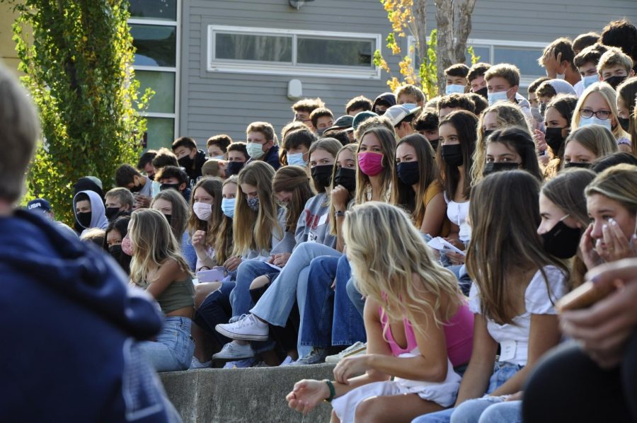 Awaiting the beginning of orientation, rising freshmen settle into the amphitheater steps.