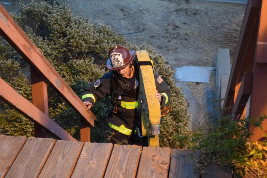 Captain Adam Vollmer of Southern Marin Fire Department carrying his equipment up a flight of stairs during fire safety training.