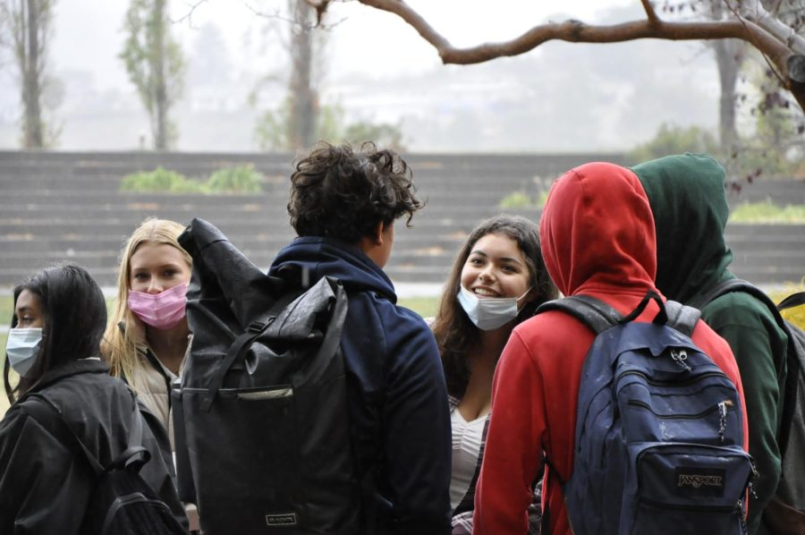 Chatting outside during their five minute break, underclassmen enjoy the rainy weather.