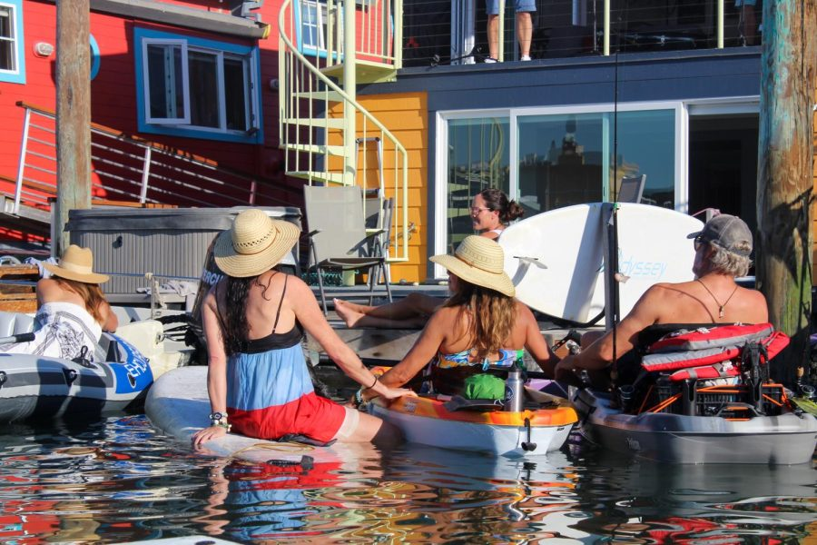 Holding each others' kayaks, audience members enjoy the community created in the Sausalito harbor.