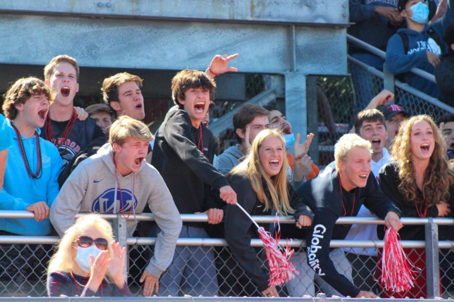 Leaning over the fence, senior students cheer for their classmates as they perform their senior skit.